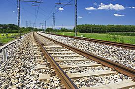 Foto van spoorrails, ondergrond van grind en blauwe licht op de achtergrond